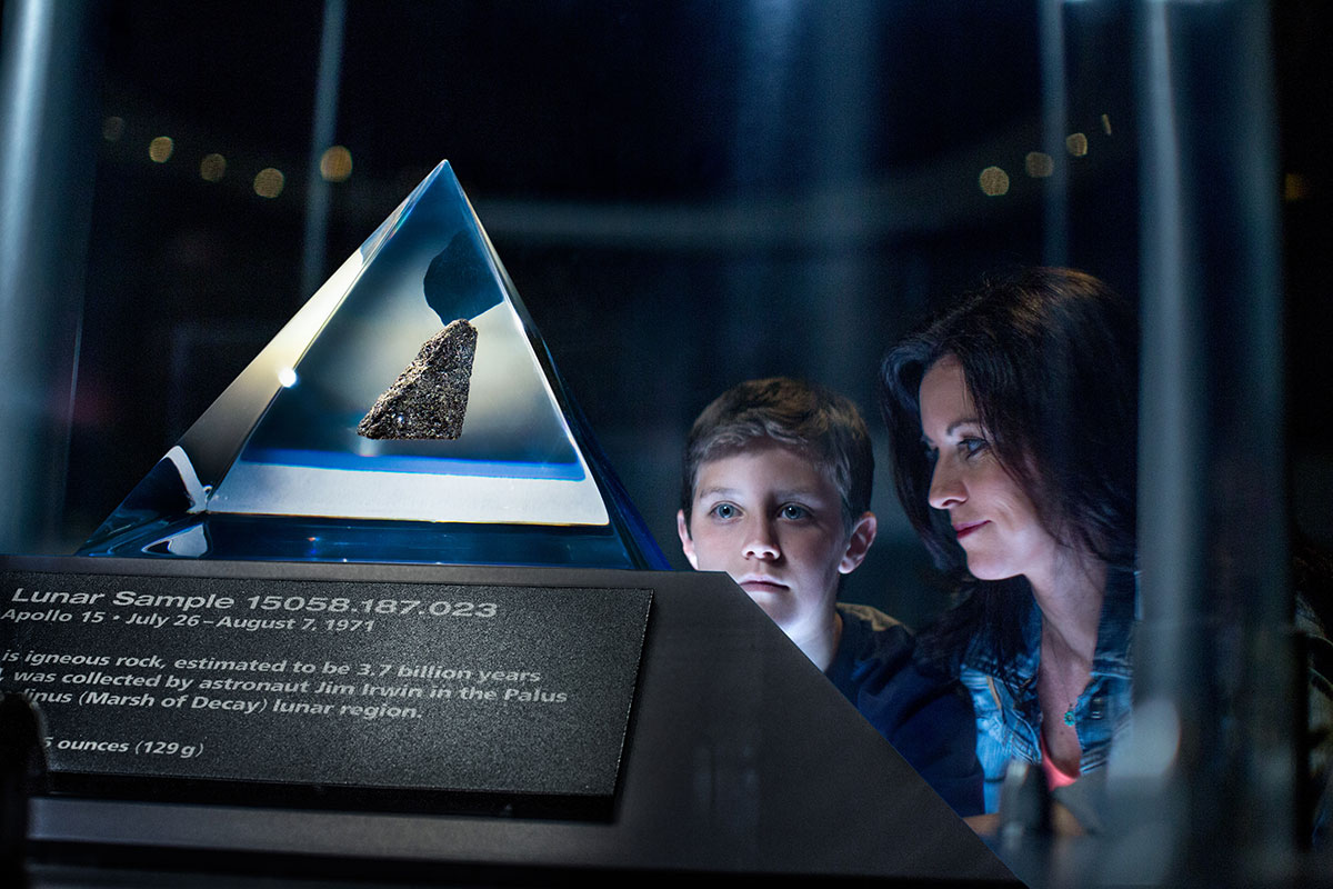 A mother and son stare at a Moon Rock at display at the Apollo Saturn V Center