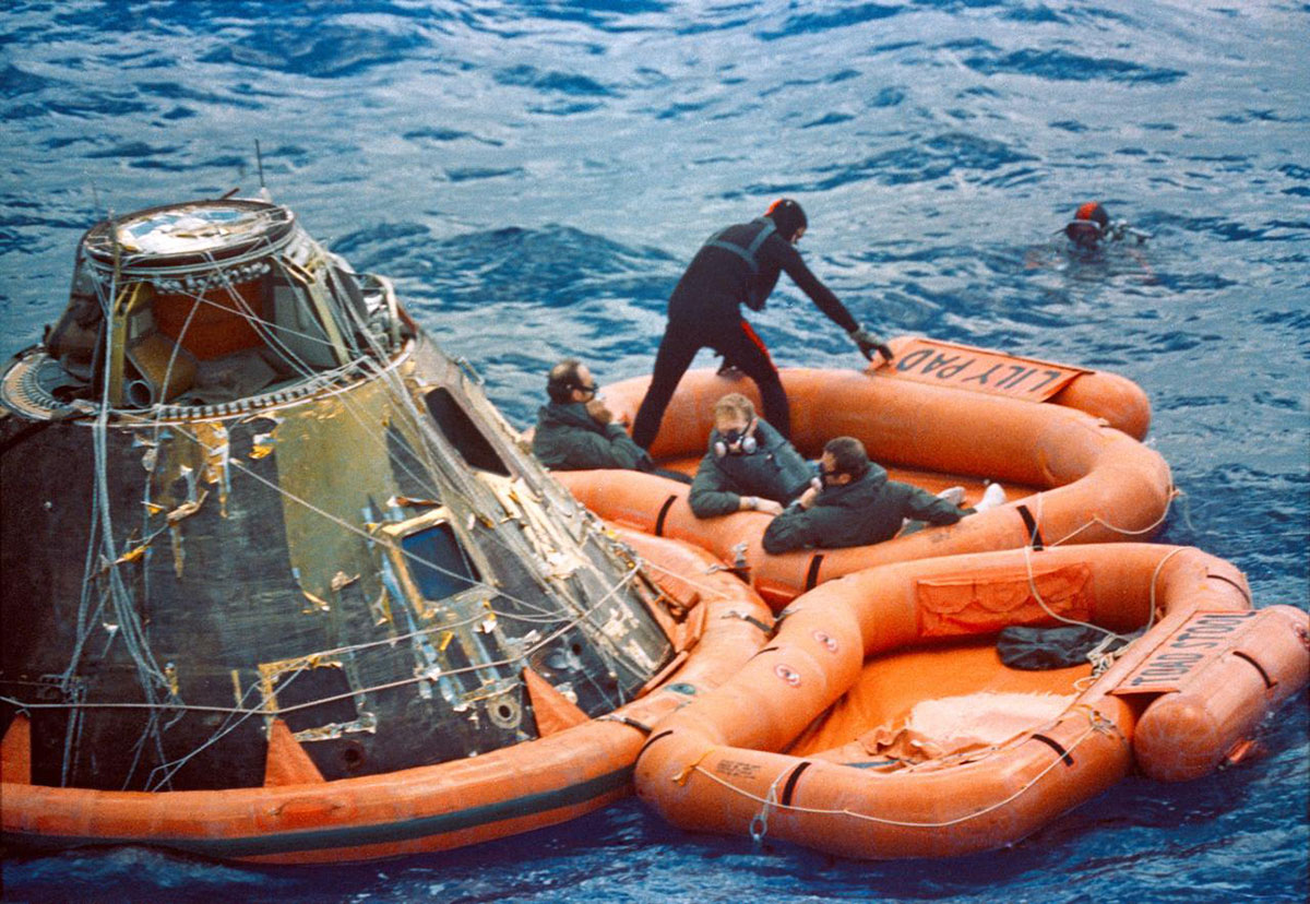 The crew of Apollo 14 sits next to their Command Module after re-entry in 1971.