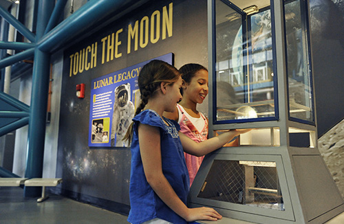 Two young girls touching a moon rock at the Apollo / Saturn V Center
