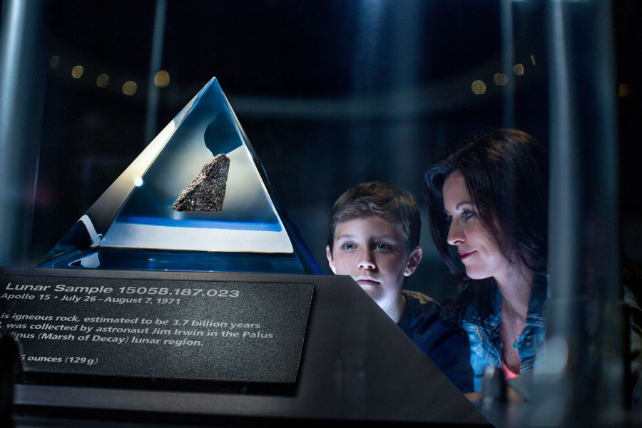 Mother and son gaze in awe at the Moon Rock on display at the Apollo/Saturn V Center