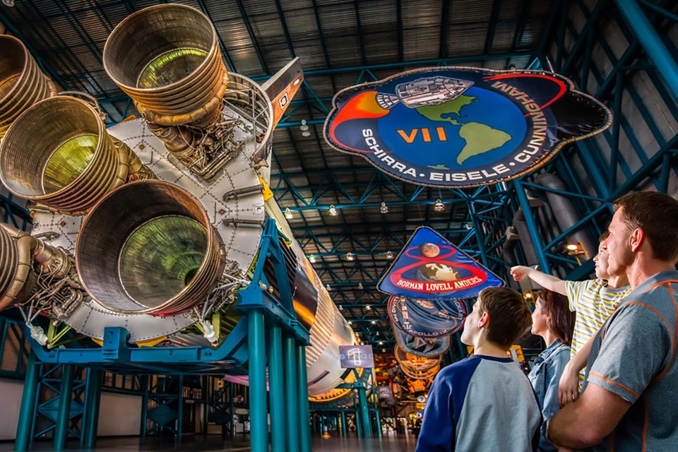Family looks up to the Saturn V moon rocket on display at the Apollo/Saturn V Center.