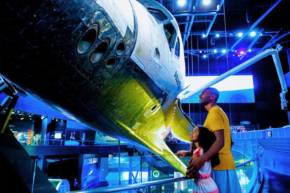 Father and daughter look up at the Space Shuttle Atlantis Orbiter on display with payload bay doors open at the Kennedy Space Center Visitor Complex.