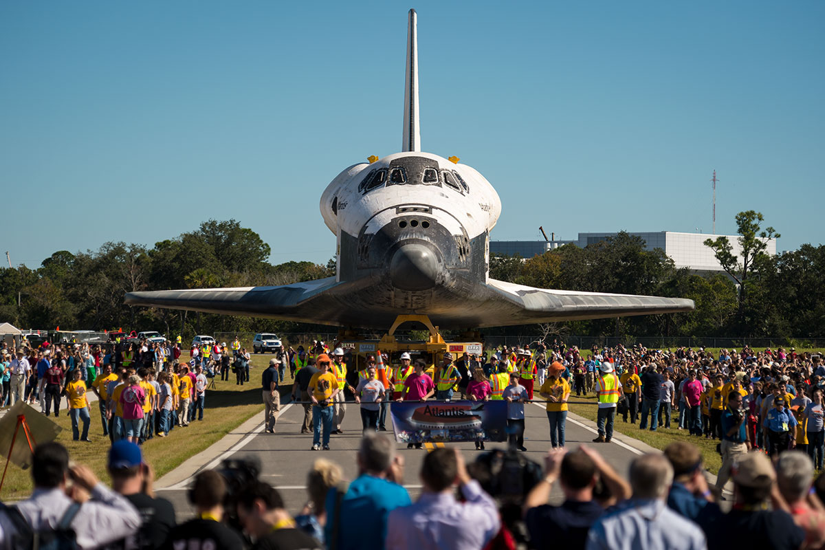 Photo of space shuttle Atlantis being brought to the Kennedy Space Center while a crowd greets it at its new exhibit.
