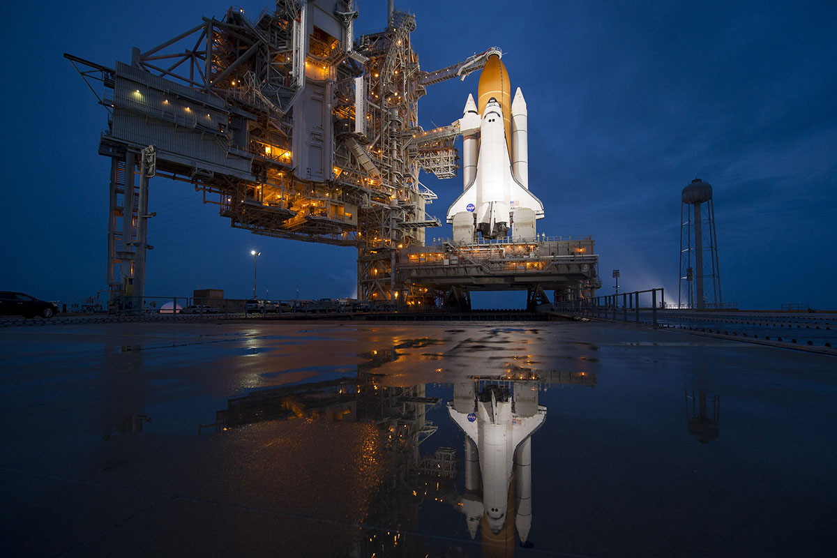 Space shuttle Atlantis sits on the Launch Pad at night in preparation for a flight.