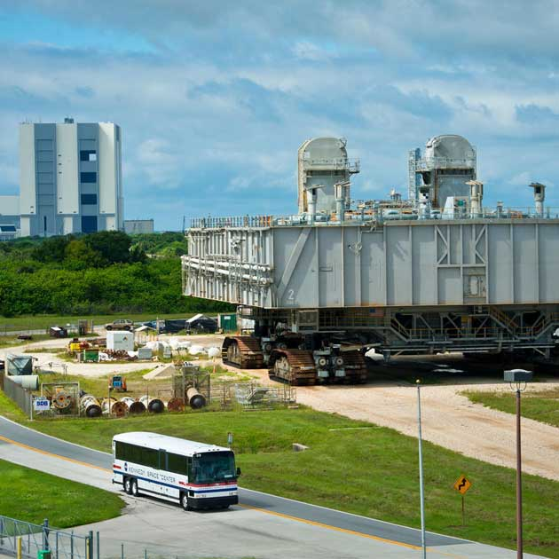 A Kennedy Space Center bus tour passes by the Vehicle Assembly building and Crawler.
