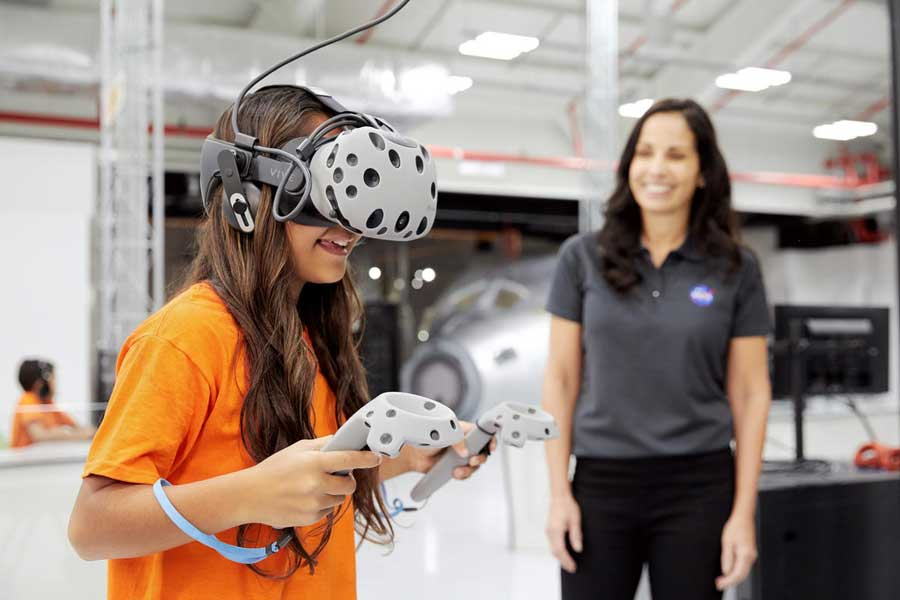 Young girl uses a Virtual Reality headset to walk on Mars.