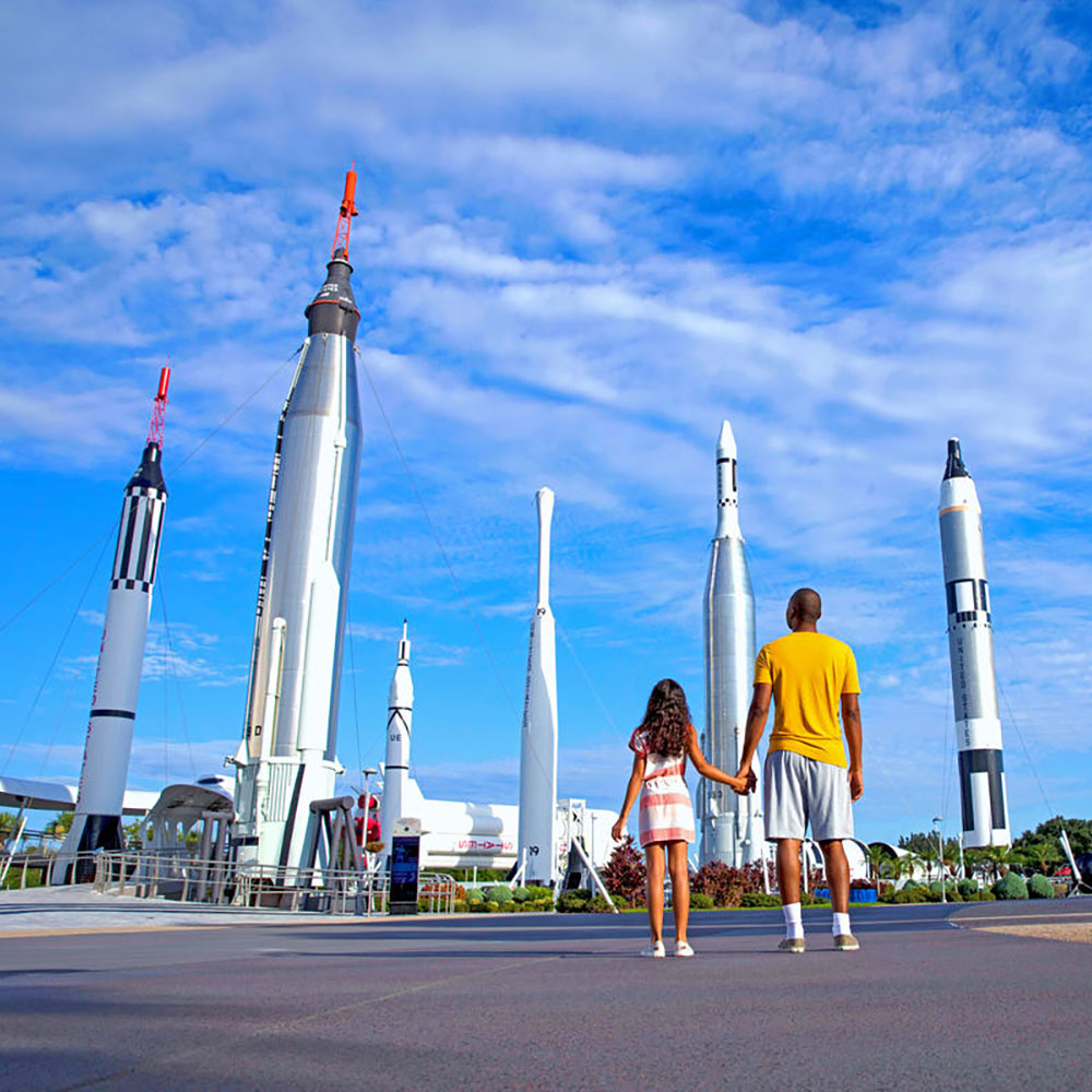 Father and daughter look up at the Rocket Garden at the Kennedy Space Center Visitor Complex.