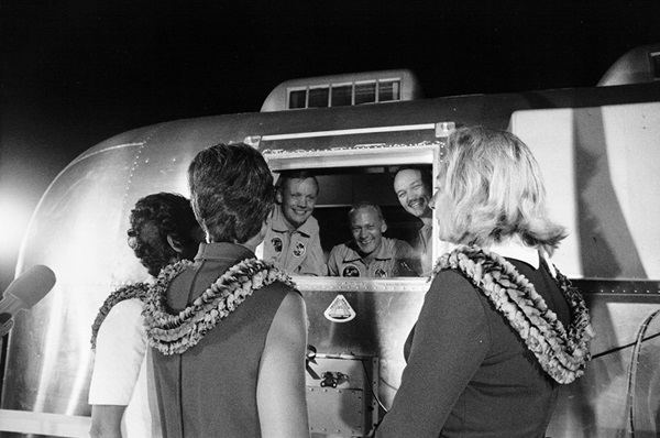 Apollo 11 astronauts looking at their wives through quarantine.