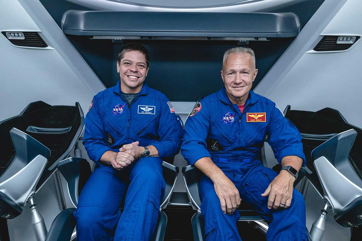 NASA astronauts, from left, Bob Behnken and Doug Hurley, assigned to fly on SpaceX's Demo-2 test flight of its Crew Dragon, are inside a mockup of the spacecraft at NASA's Johnson Space Center in Houston on Aug. 2, 2018, ahead of the agency's announcement of their commercial crew assignment.