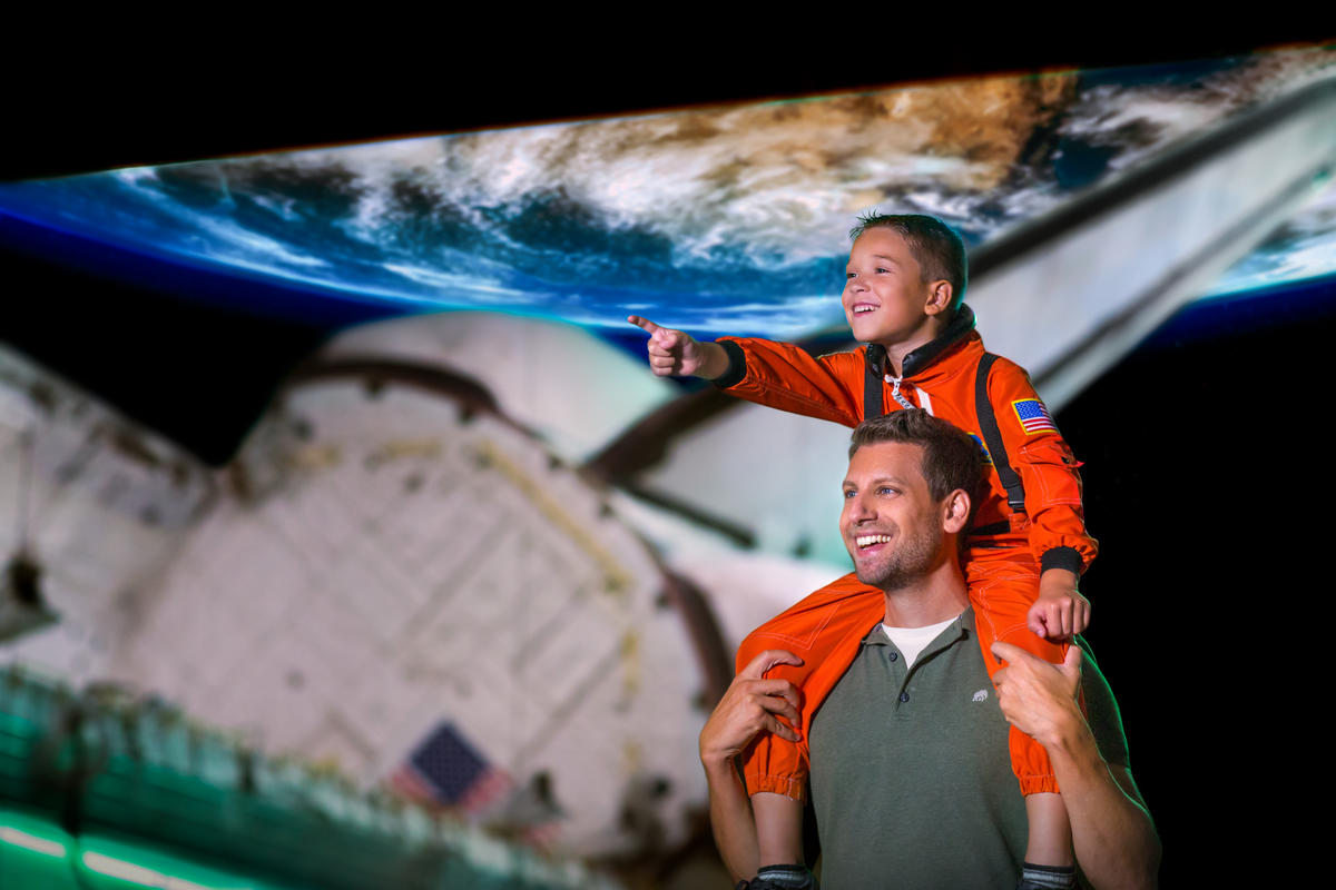 Father with son on his shoulders touring Space Shuttle Atlantis.