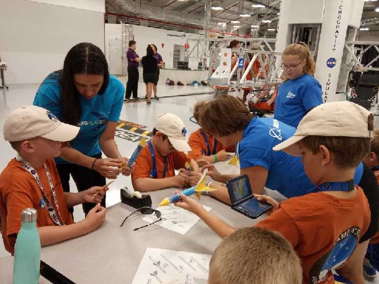 Boeing volunteers assist in Camp KSC campers in building their stomp rockets.