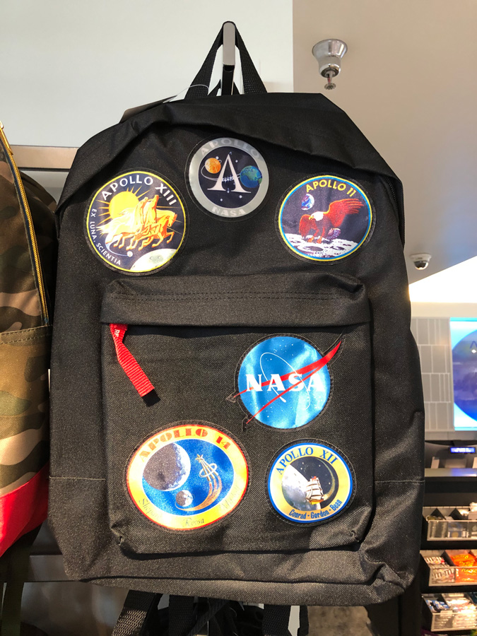 Backpack with various mission patches on it.