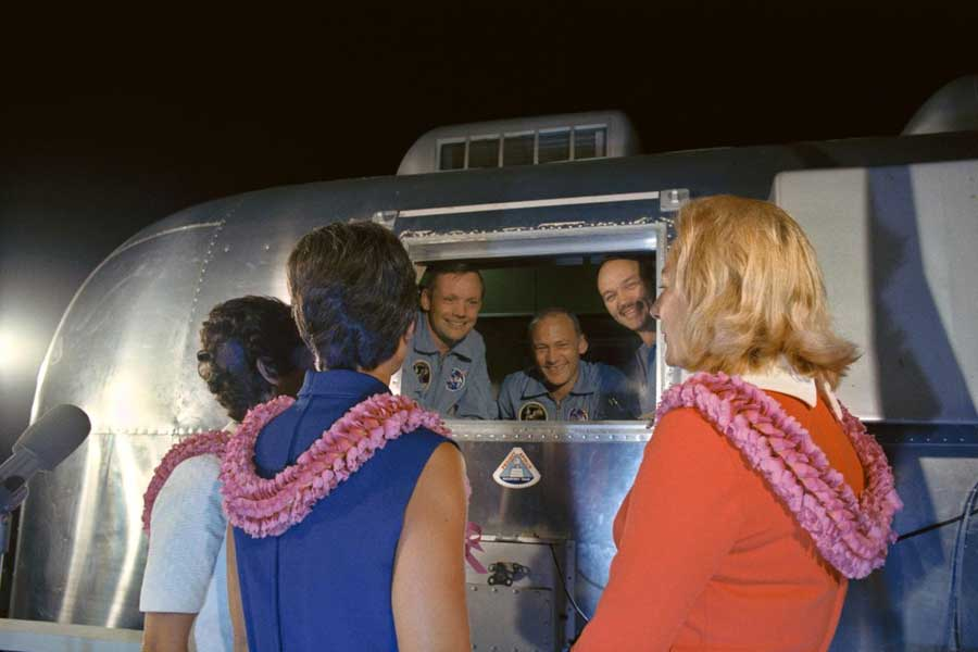 The Apollo 11 crewmen, still under a 21-day quarantine, are greeted by their wives.