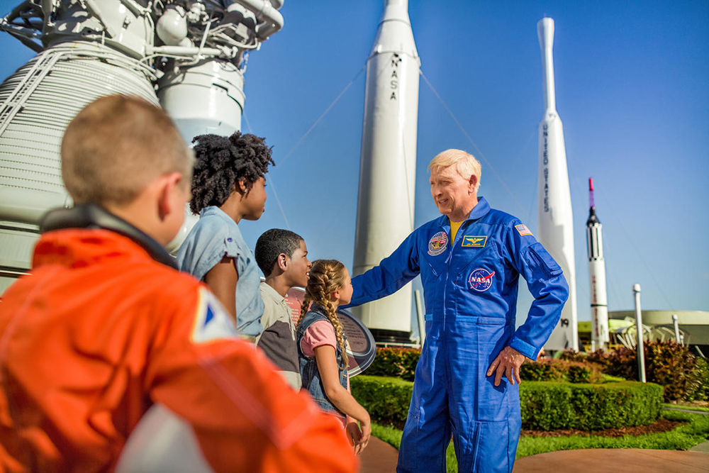 Guests touring the Rocket Garden with Astronaut Jon McBride at Kennedy Space Center Visitor Complex.