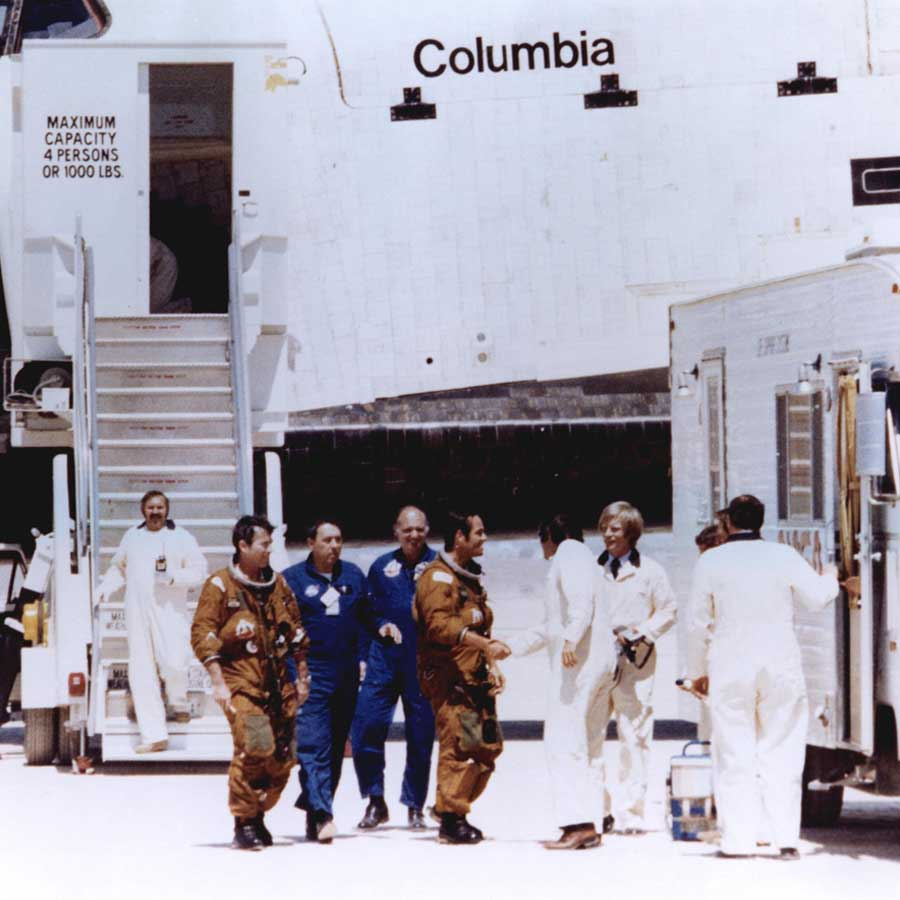 Space Shuttle astronauts John Young and Robert Crippen (in tan space suits) are greeted by members of the ground crew moments after stepping off the shuttle Columbia following its first landing at Edwards Air Force Base, Calif. Young and Crippen had piloted the Columbia on its first orbital space mission, April 12 - 14, 1981.