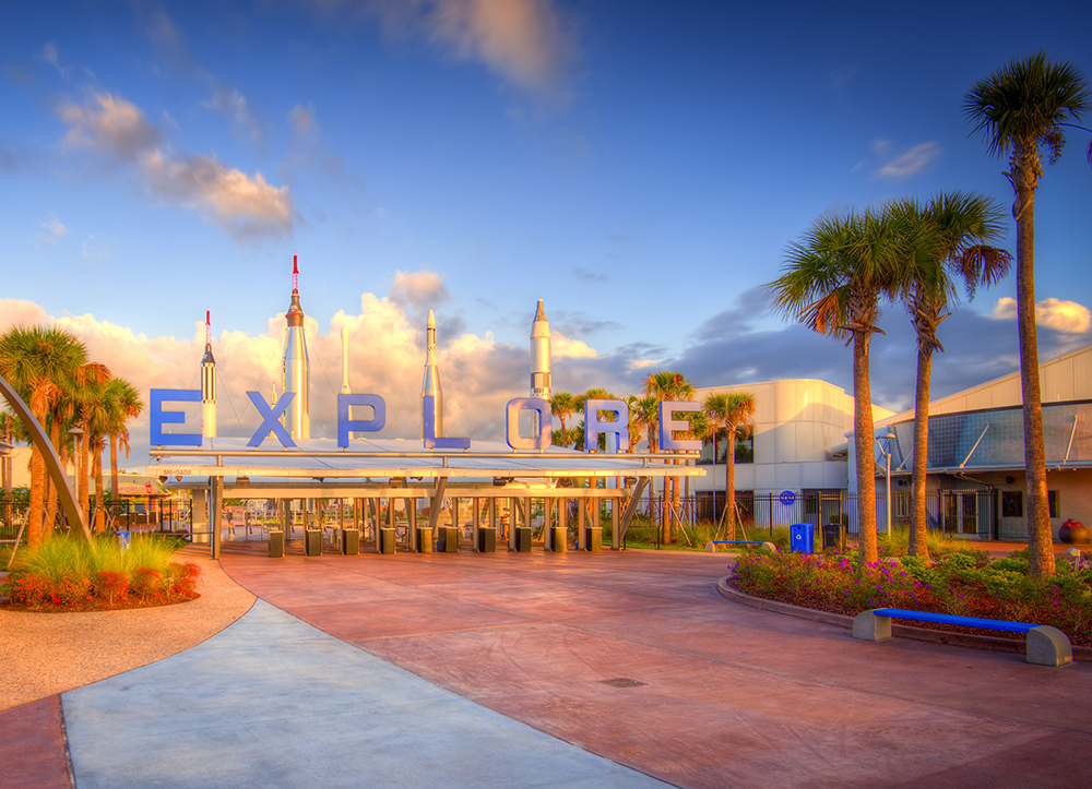 "The front entrance of the Kennedy Space Center Visitor Complex, prominently featuring ""Explore""."