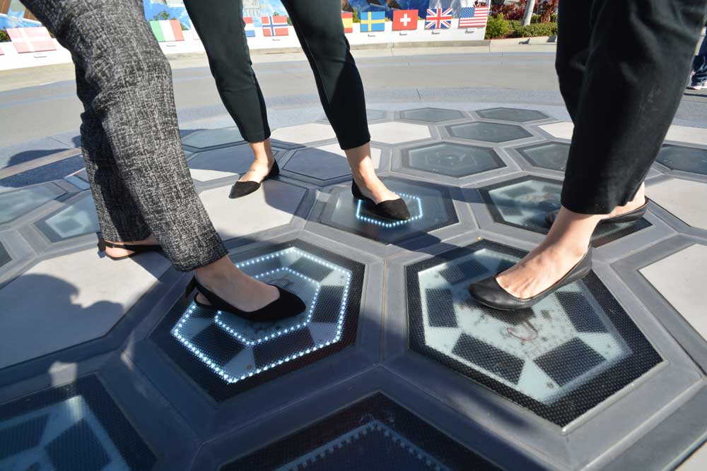 Guests lighting up the Step. Tower. Launch! power tiles using piezoelectric energy.