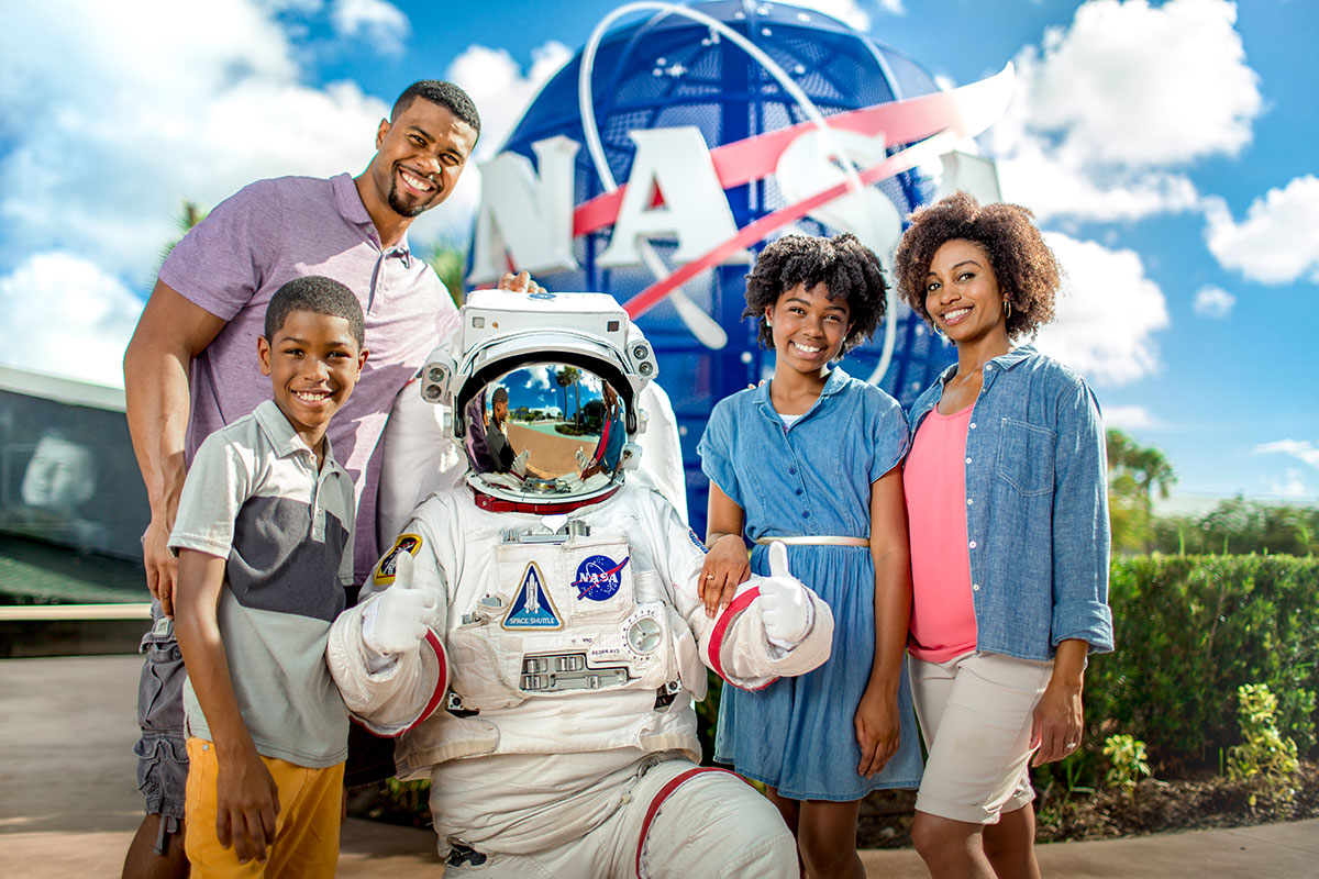 Family poses for a photo with an astronaut in front of the NASA meatball at Kennedy Space Center Visitor Complex.