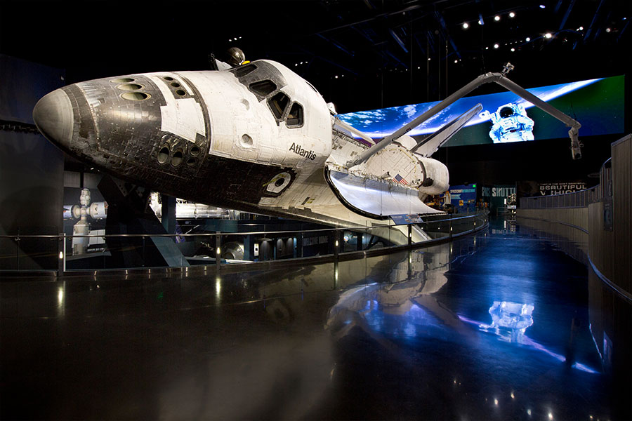 Atlantis is displayed as only astronauts have seen her in space, rotated 43.21 degrees with payload doors open and Canadarm extended, as if just undocked from the International Space Station (ISS).