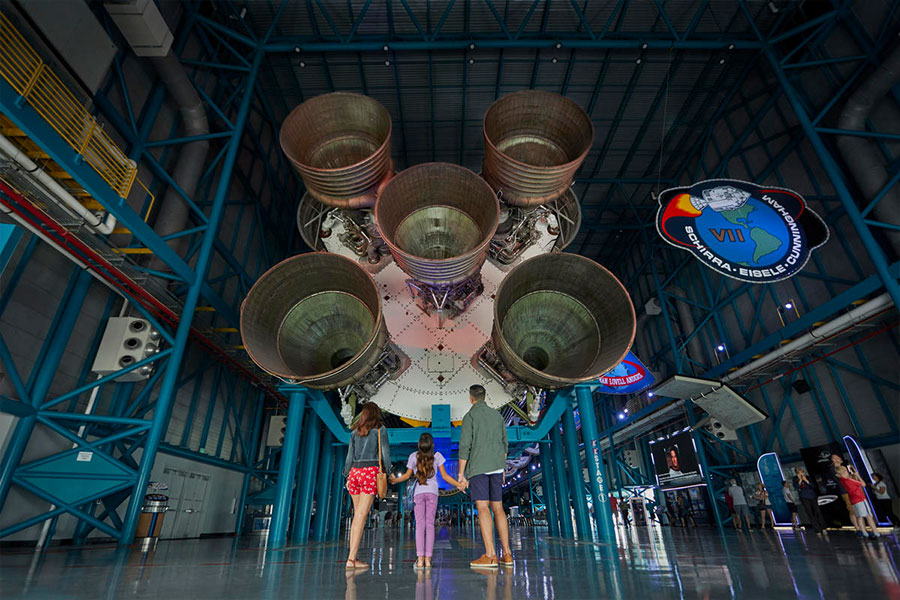 Family stares up in awe at Saturn V Rocket on display at Kennedy Space Center Visitor Complex.