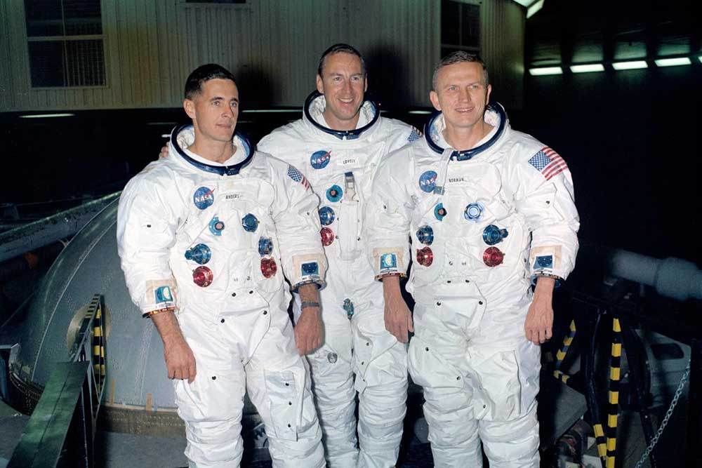 The prime crew of the Apollo 8 lunar orbit mission stands beside the gondola in Building 29 after training. Astronauts left to right are William Anders, James Lovell and Frank Borman.
