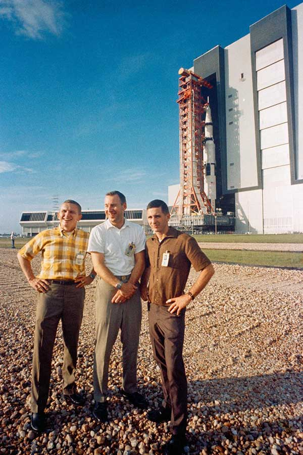 The Apollo 8 prime crew stands in foreground as the Apollo (Spacecraft 103/Saturn 503) space vehicle leaves the Kennedy Space Center's Vehicle Assembly Building on way to Pad A, Launch Complex 39.