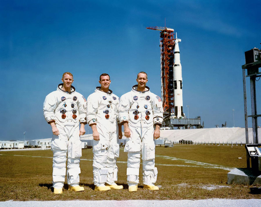 These three astronauts are the prime crew of the Apollo 9 Earth-orbital space mission. Left to right, are Russell L. Schweickart, lunar module pilot; David R. Scott, command module pilot; and James A. McDivitt, commander. In the right background is the Apollo 9 space vehicle on Pad A, Launch Complex 39, Kennedy Space Center (KSC).
