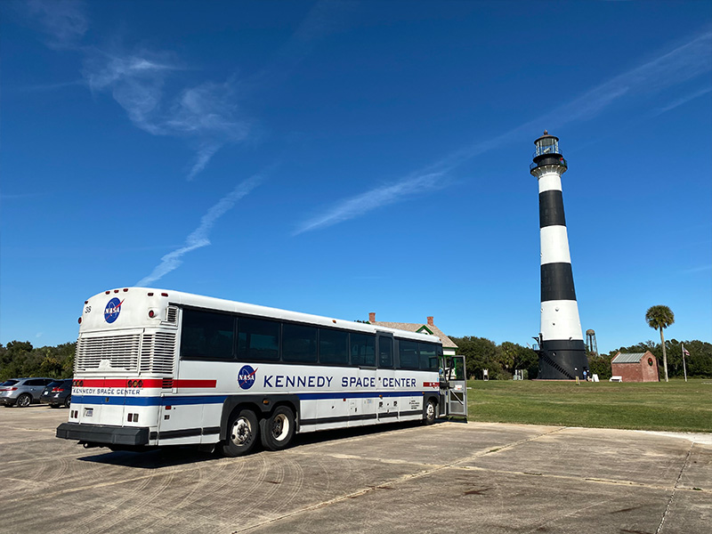 The Cape Canaveral Lighthouse and a Kennedy Space Center Visitor Complex bus.