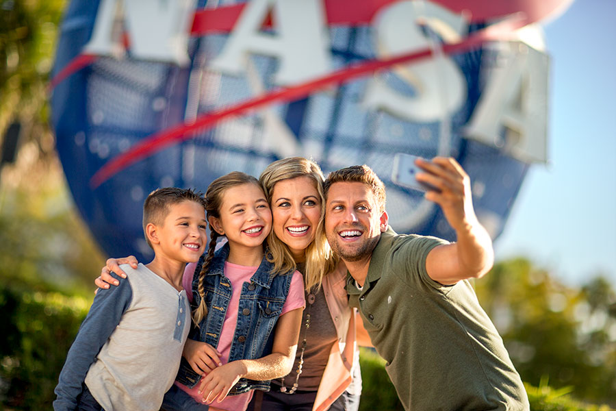 Family taking a selfie at the park entrance next to the NASA meatball