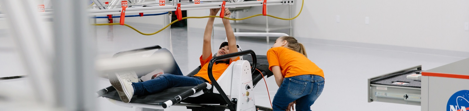 Two kids using the microgravity chair to experience how astronauts repair the International Space Station