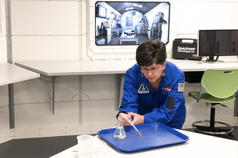 A Kennedy Space Center Visitor Complex educator conducts an experiment on water surface tension.