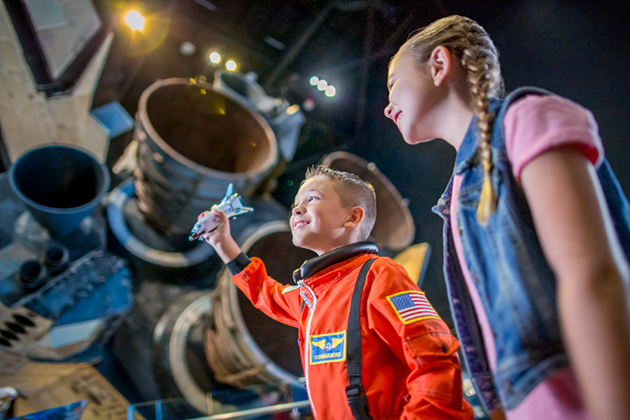 Two children explore the Space Shuttle Atlantis attraction at Kennedy Space Center Visitor Complex.