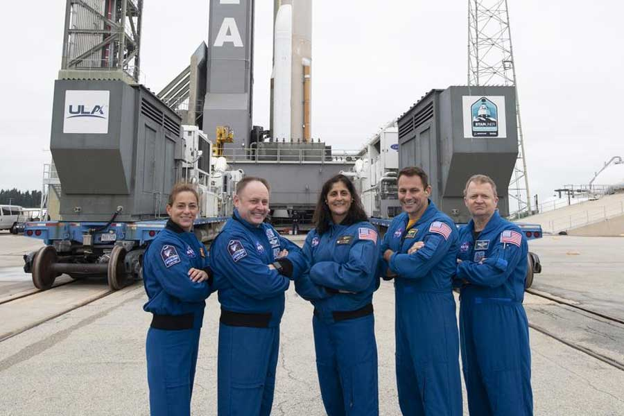 NASA astronauts Nicole Mann, Michael Fincke, Suni Williams, Josh Cassada, and Eric Boe pose for a picture after a United Launch Alliance Atlas V rocket with Boeing's CST-100 Starliner spacecraft onboard was rollout out to the launch pad at Space Launch Complex 41 ahead of the Orbital Flight Test mission, Wednesday, Dec. 18, 2019 at Cape Canaveral Air Force Station in Florida.