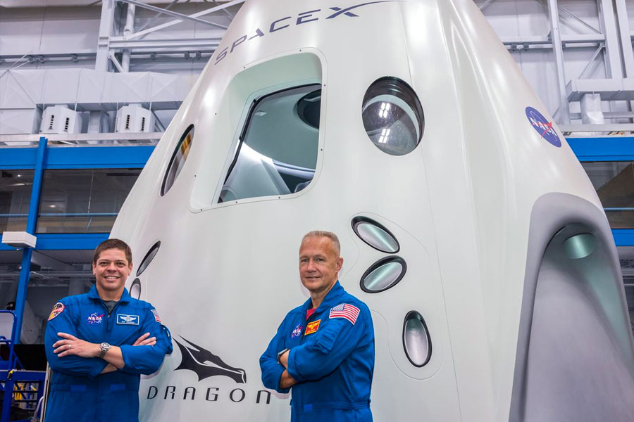 NASA astronauts Bob Behnken (left) and Doug Hurley pose for a portrait in front of the SpaceX Dragon Commercial Crew vehicle mock up.