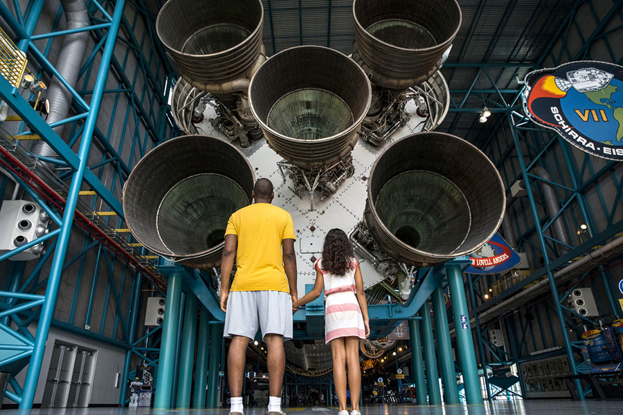 Father and daughter look up at the Saturn V rocket on display at the Apollo/Saturn V Center at Kennedy Space Center Visitor Complex.