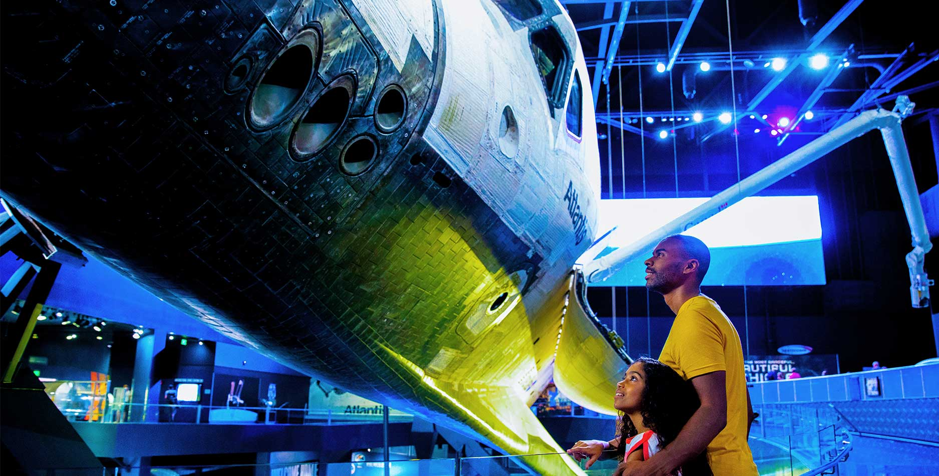 Father and daughter look up at space shuttle Atlantis